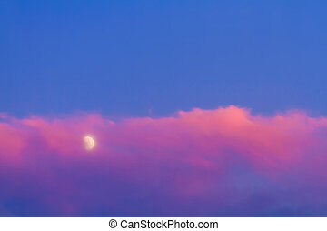 Moon under pink cloud on blue sky background