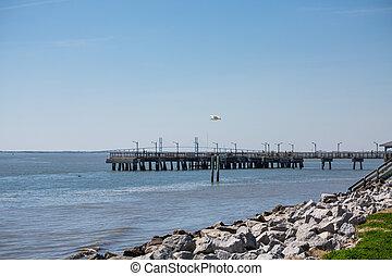 Pier by Rock Seawall - A rock seawall leading toward an old...