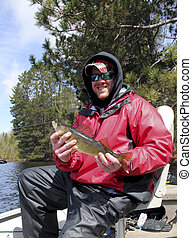 walleye and fisherman - fisherman holding a walleye in a...