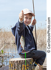 Boy while fishing - Happy boy holding a fish caught in the...
