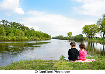 Brother and little sister sitting on the bank of the river -...