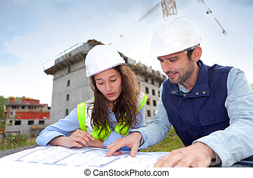 Co-workers working on a construction site - View of...