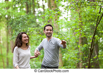 Young couple having a walk in a forest - View of a Young...