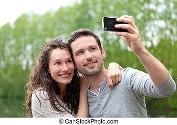 Young couple taking selfie picture at the park - View of a...