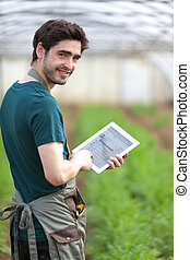 Young business farmer working on his tablet - View of a...