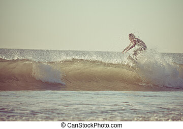 Surfing in the early morning with retro effect.