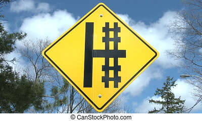 Cross sign close to railway tracks - Yellow cross sign close...