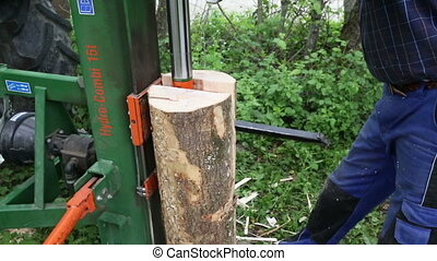 Hydraulic wood splitter - Worker using a hydraulic wood...