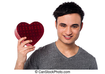 Young man holding heart shaped box - Smiling man with...