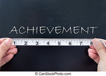 Measuring achievement - Tape measure aligned against...