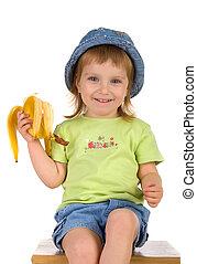 Little girl eats a banana