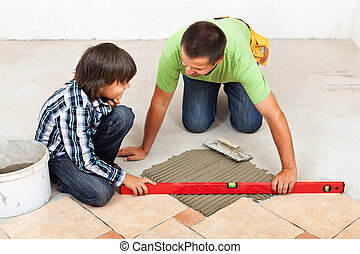 Man and boy laying ceramic floor tiles together