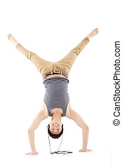 young man doing a handstand against and listening music