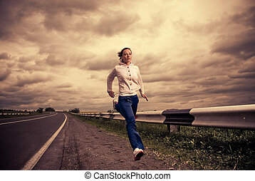 running woman - young sportive woman running at stormy...