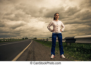 strong woman - young pretty strong woman at stormy roadside