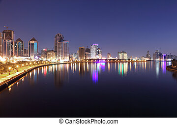 Skyline of Sharjah City at dusk, United Arab Emirates
