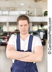 Young handsome mechanic in car dealership Place for text