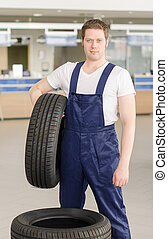 Young mechanic with tire in service center.
