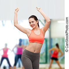 smiling teenage girl in sportswear dancing - fitness and...