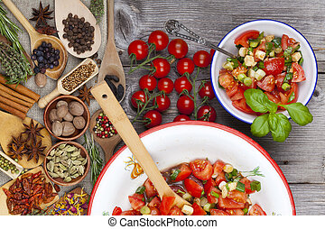 Tomato salad an enamel bowl on rustic wooden table