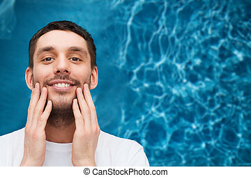 beautiful smiling man touching his face - health and beauty...
