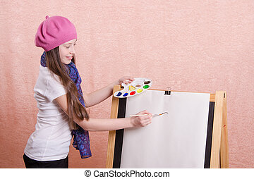 girl begins to draw picture on the easel - Twelve year old...