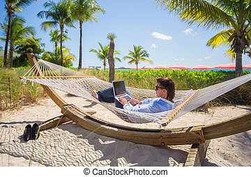 Young man working on laptop in hammock at tropical beach -...