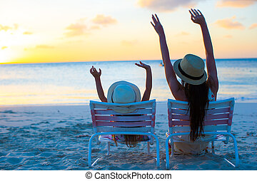 Little girl and mother sitting on beach chairs at sunset -...
