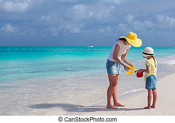 Mother and little daughter on the beach during their...