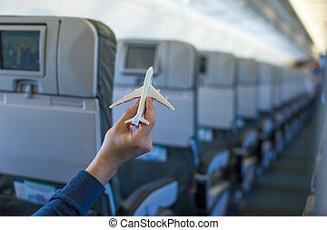 Close up hand holding an airplane model inside a large...