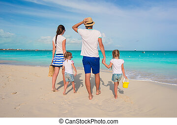 Back view of beautiful family with two kids on tropical...