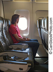 Young man looking in window on board of an airplane during the flight