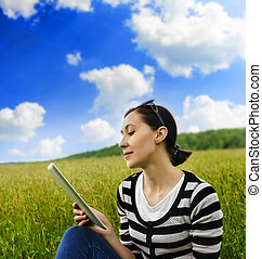 Girl with tablet pc on the grass.
