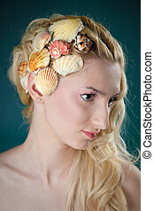 beautiful girl with little shells in her hair-do