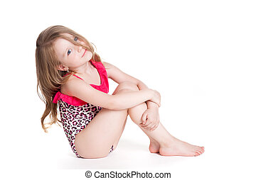 little blonde happy girl in pink swimsuit sitting on the...