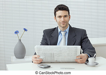 Businessman reading newspaper - Young businessman having...