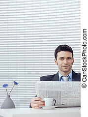 Businessman with newspaper - Young businessman sitting at...