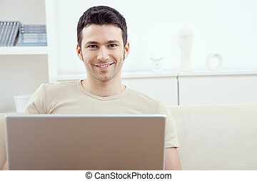 Man using laptop at home - Happy young man sitting on couch...
