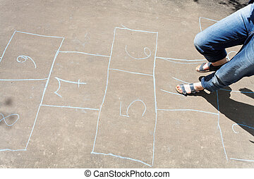 playing in hopscotch outdoors in sunny day