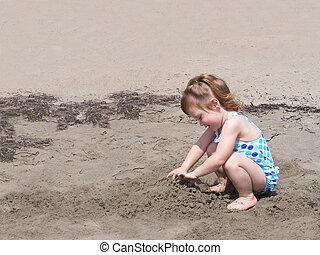Child playng in beach sand - A little girl digs in the beach...
