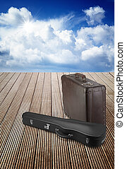 old suitcase and violin case on wooden terrace
