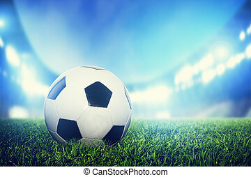 Football, soccer match. A leather ball on grass on the stadium
