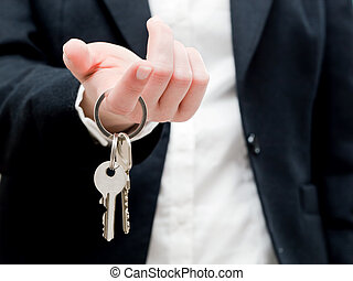 A real estate agent holding keys to a new house in her...