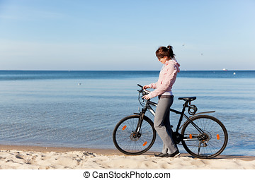 Young woman tracking her route on smartphone gps. Bicycle...