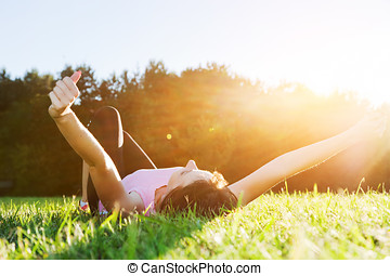 Young beautiful woman lying, relaxing and stretching on the grass