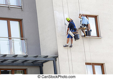 Working at height - Building maintenance: Men working at...