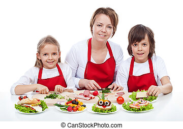 Woman and kids making creative food creature sandwiches...