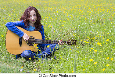 Young woman playing an acoutic guitar in the fields - Young...