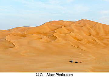 People with tents and cars among dunes in Rub al-Khali...