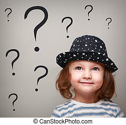 Happy thinking kid girl in hat looking up on many questions above the head